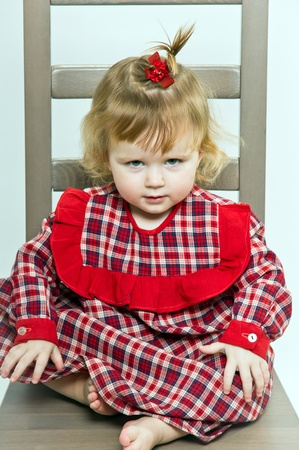 Cute little girl in red dress posing on a chair Stock Photo - 12409783