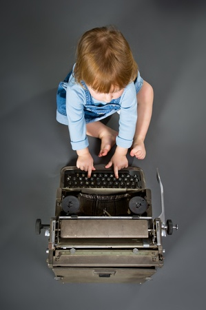 Cute little baby with retro style typewriter in studio photo