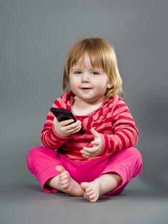 Niña linda con el teléfono móvil en el fondo gris Foto de archivo - 12831328