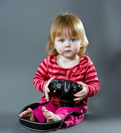 Cute little baby with digital photo camera on gray background