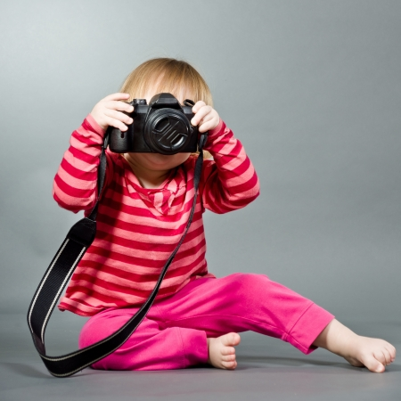 look at camera: Cute little baby with digital photo camera on gray background