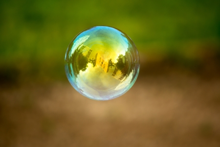 soap bubbles: Soap buble flying. Houses reflected in. Stock Photo