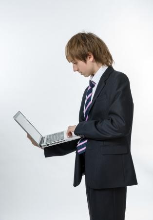 composure: Teenage ragazzo che lavora nel computer portatile bianco. Concentrazione e compostezza.