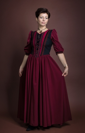 medieval dress: Young woman portrait in red dress on brown background