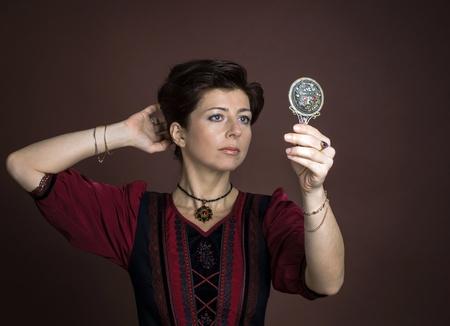 primp: Ritratto di giovane donna con specchio su sfondo marrone