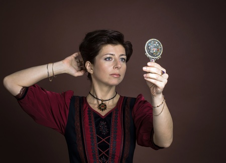 Young woman portrait with mirror on brown background Stock Photo - 18336646