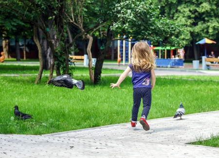 Cute little girl frighting pigeons on playground photo