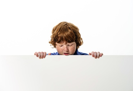 carroty: Freckled red-hair boy showing to the white board. Isolated on white background. Stock Photo