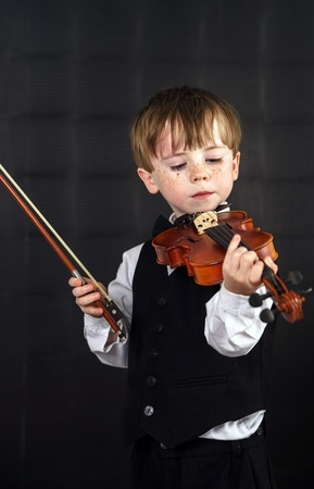 Freckled red-hair boy playing violin. Young musician. photo