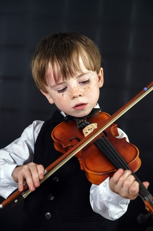 jazzbow: Freckled red-hair boy playing violin. Young musician.