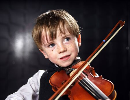 carroty: Freckled red-hair boy playing violin. Young musician.