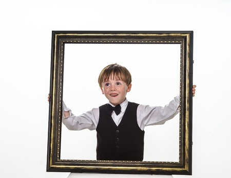 jazzbow: Freckled red-hair little boy with big picture frame. Isolated on white background.
