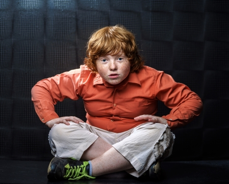 Freckled red-hair boy posing on dark background. Emotions.