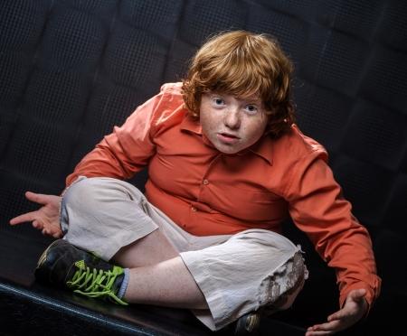 exasperate: Freckled red-hair boy posing on dark background. Emotions.