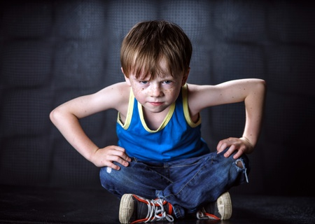 impressive: Freckled red-hair boy posing on dark background. Emotions.