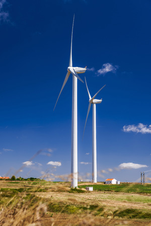 Wind turbine generating electricity on blue sky background photo