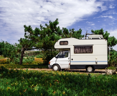 Touristic caravan staying in a forest. Comfort and freedom. Standard-Bild