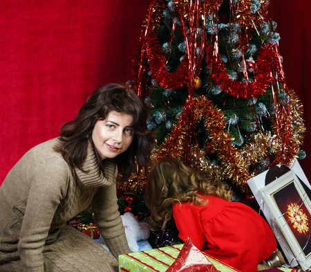 Mother with little daughter finding christmas gifts over the tree Stock Photo - 25151142
