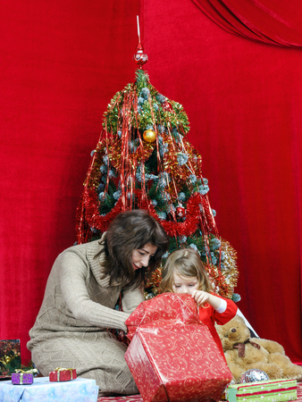 Mother with little daughter finding christmas gifts over the tree Stock Photo - 25151173