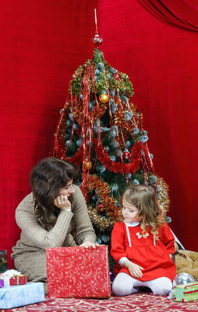 Mother with little daughter finding christmas gifts over the tree photo