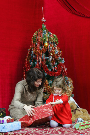 Mother with little daughter finding christmas gifts over the tree Stock Photo - 25151177