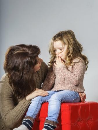 ojos tristes: Madre tranquilizador pequeña hija. Ella se distrae y llorando
