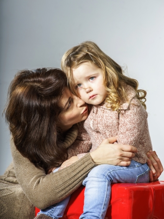 crying child: Mother reassuring little daughter. She is distracted and crying