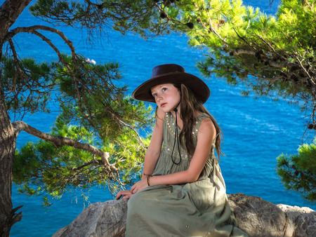 reverie: Reverie young girl sitting in a forest on seaside Stock Photo