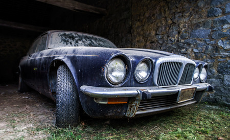 Old retro rusty car in village garage. American style of 70. Stock Photo
