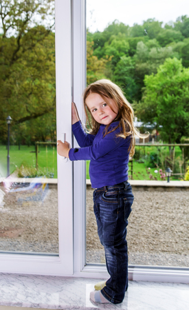 Cute little girl and pvc window. Big frame . View to the yard.