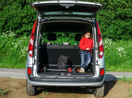 vacance: Piccolo viaggiatore stare nel bagaglio dell'auto. Viaggio di famiglia.