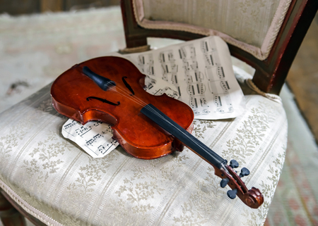 Antique violin and vintage music notes in old house photo
