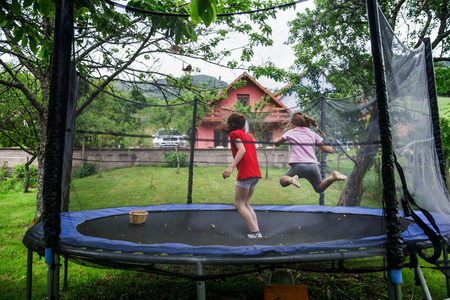 Two happy sisters on trampoline, children leisure Standard-Bild
