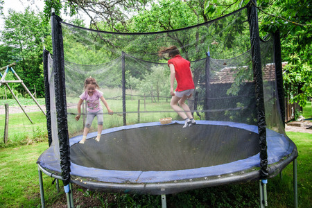 Two happy sisters on trampoline, children leisure photo