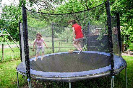 Two happy sisters on trampoline, children leisure Standard-Bild
