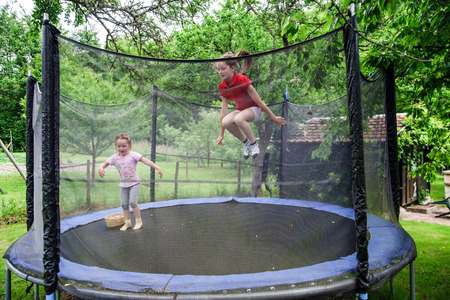 Two happy sisters on trampoline, children leisure Stockfoto