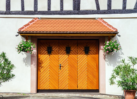 Renovated wooden garage doors in old house, Alsace, France Stock Photo