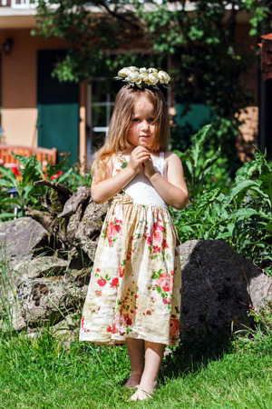chaplet: Cute little girl with flowers chaplet in summer garden Stock Photo