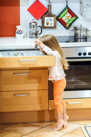 the case before: Little girl getting tableware from table case before dinner Stock Photo