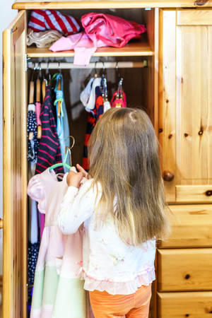garderobe: Cute little girl hanging up her clothes into the wardrobe Stock Photo