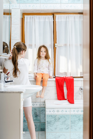 Cute little girl sitting on a bathroom window in the house photo