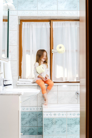 Cute little girl playing with toilet paper roll in a bathroom photo
