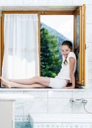 Teenage girl sitting on bathroom window in the house photo