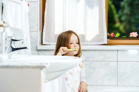 Little girl cleaning the teeth in bathroom, morning photo