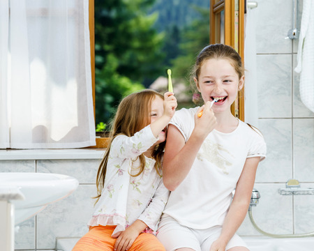 Two sisters cleaning the teeth together, morning, bathroom Standard-Bild