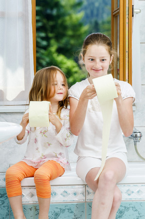 Two sisters playing with toilet paper roll in bathroom photo