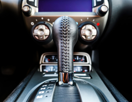 Luxury car interior details. Transmission handle, skin. Stock Photo