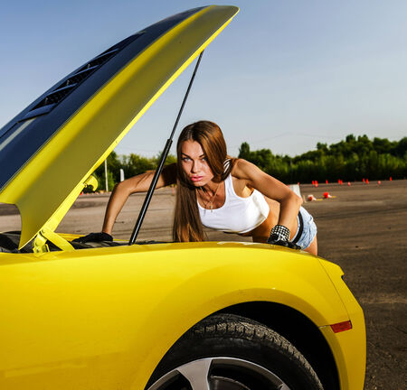 Luxury glamour girl posing with yellow sport car photo