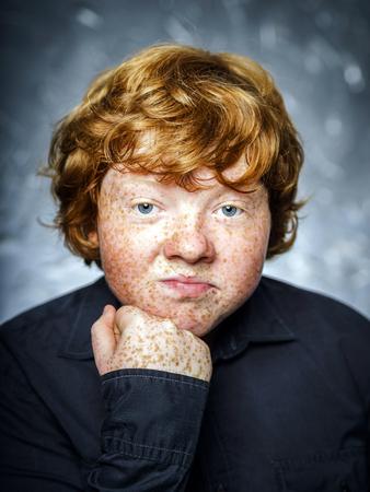 malcontent: Fat freckled boy studio portrait in dark background