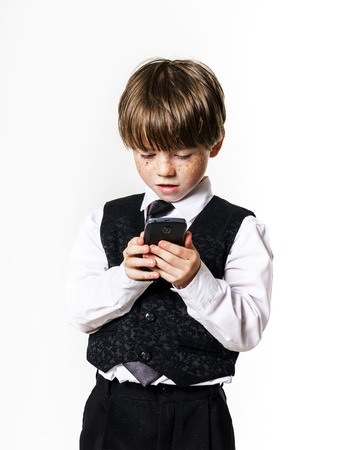 jazzbow: Emotional red-haired boy calling by  mobile phone Stock Photo